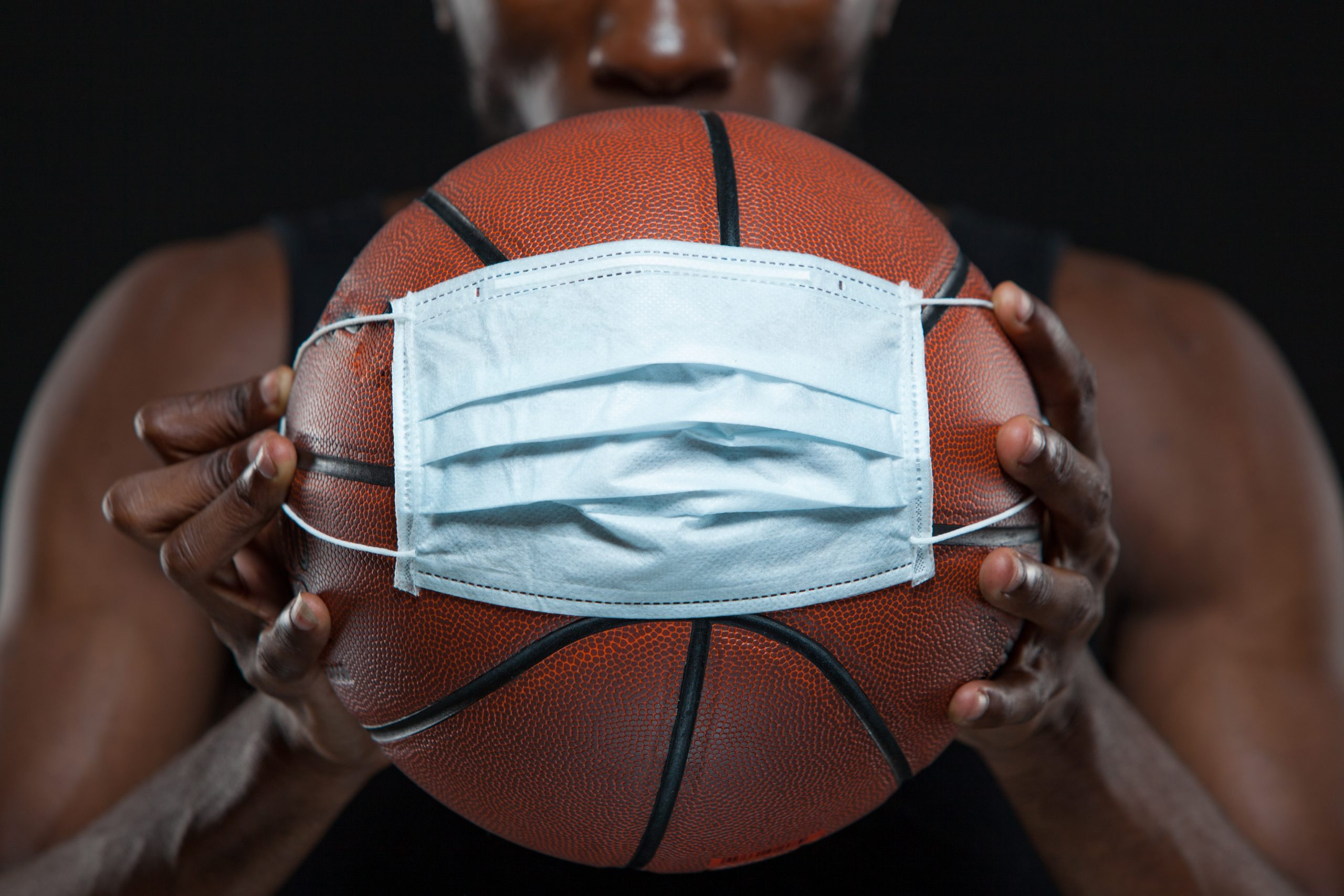 basketball with mask held by player